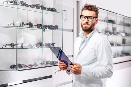 Um oftalmologista bonito com receita na pasta escolhendo um par de óculos. Optometrista checando a vitrine com óculos na loja ou no hospital.