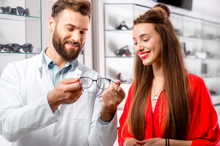 Handsome ophthalmologist showing eyeglasses to the young female patient in front of the showcase with eyeglesses in the hospital Stock Photo