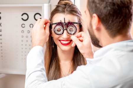eye doctor: Ophthalmologist wearing try-on tool for vision check to the young female patient in front of the eye chart in the cabinet. Eye doctor with patient in the clinic