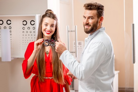 eye doctor: Ophthalmologist giving try-on tool for vision check to the young female patient in front of the eye chart in the cabinet. Eye doctor with patient in the clinic