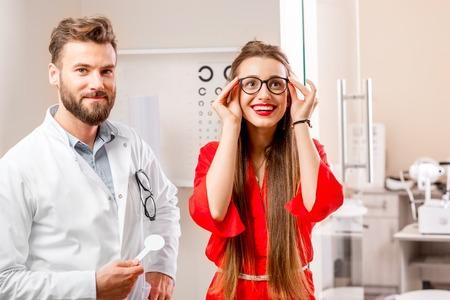 젊고 행복한 여성 환자가 새로운 안과 의사와 안과 의사에게 시도하고 캐비닛에 스톡 콘텐츠