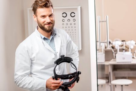 optician: Eye doctor with ophthalmologic binocular device for checking vision with the eye chart on the background in the cabinet