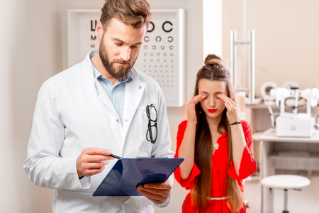 eye doctor: Eye doctor writing medical recipe standing in the cabinet with unhappy female patient. Eye diseases and problems with vision