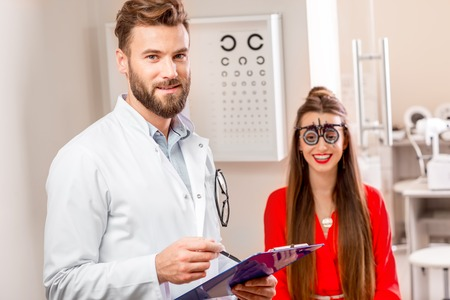 Eye doctor writing medical recipe standing in the cabinet with happy female patient Stock Photo