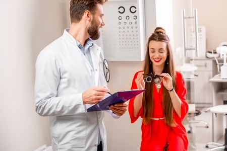 eye doctor: Eye doctor writing medical recipe standing in the cabinet with happy female patient Stock Photo