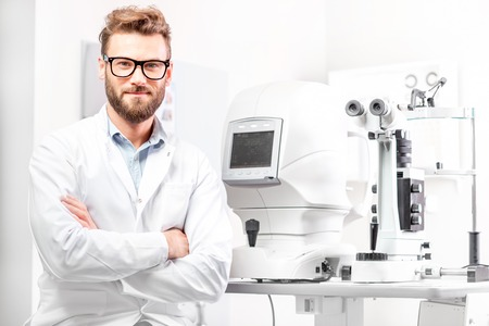eye doctor: Portrait of handsome eye doctor sitting with ophthalmologic device in the cabinet
