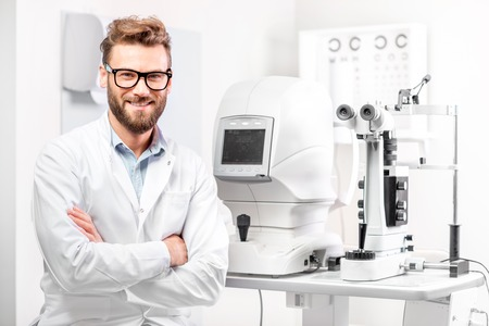 キャビネット内の眼科デバイスと座っているハンサムな眼科医の肖像画