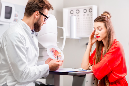 eye doctor: Eye doctor with young female patient having cosultation in the ophthalmologic cabinet. Eye diseases and problems with vision Stock Photo