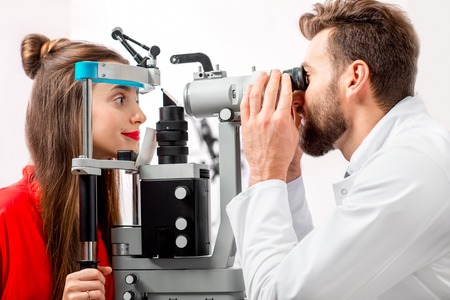 eye doctor: Eye doctor checking vision of young female patient with ophthalmologic device in the cabinet Stock Photo