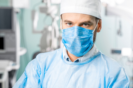 surgeons hat: Portrait of surgeon in operating room with surgical microscope on the background Stock Photo