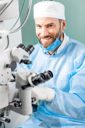 surgeons hat: Portrait of smiling eye surgeon in uniform with microscope in the operating room