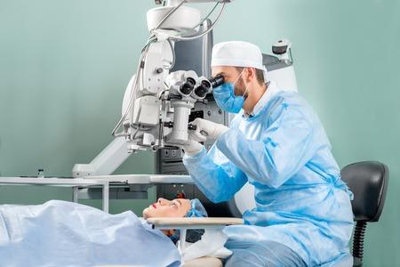 Chirurg op zoek naar de microscoop in het oog van vrouwelijke patiënt bij de operatiekamer Stockfoto