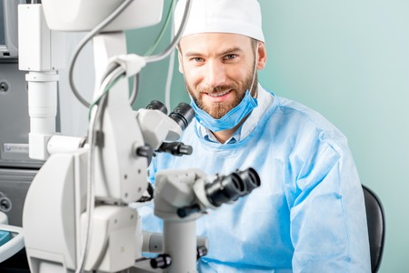 Portrait of smiling eye surgeon in uniform with microscope in the operating room