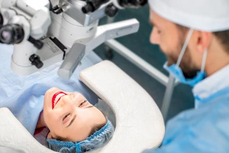 Gelukkige patiënt die met chirurg spreken die op de laag vóór de verrichting in de werkende ruimte liggen