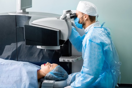 Eye surgeon operating woman with laser vision correction machine in the operating room