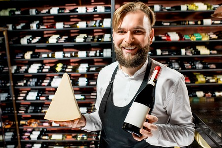 choise: Portrait of a sommelier in uniform with parmegiano cheese and bottle of wine at the restaurant or supermarket. Choosing wine according to the type of cheese. Bottle with empty label to copy paste Stock Photo