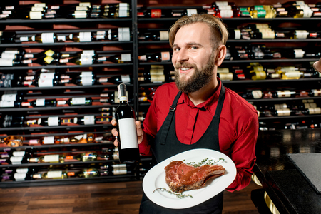 choise: Portrait of a seller or sommelier with wine bottle and steak on the plate at the luxury supermarket or restaurant. Choosing wine according to the type of meat. Bottle with empty label to copy paste