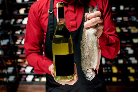 Food seller holding wine bottle and trout fish at the luxury supermarket or restaurant. Choosing wine according to the type of fish. Bottle with empty label to copy paste