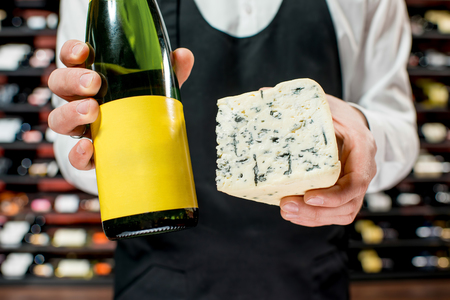 choise: Food seller holding a bottle of white wine and a pieace of blue cheese. Choosing wine according to the type of cheese. Bottle with empty label to copy paste