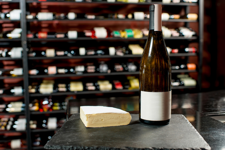 choise: A bottle of white wine with a piece of brie cheese on the black board in supermarket or restaurant . Bottle with empty label to copy paste Stock Photo