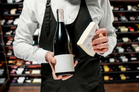 Food seller holding a bottle of white wine and a pieace of brie cheese. Choosing wine according to the type of cheese. Bottle with empty label to copy paste