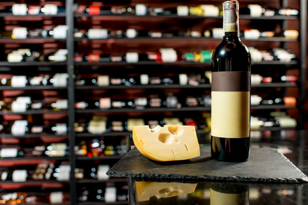 choise: A bottle of wine with a piece of gouda cheese on the black board in supermarket or restaurant . Bottle with empty label to copy paste Stock Photo