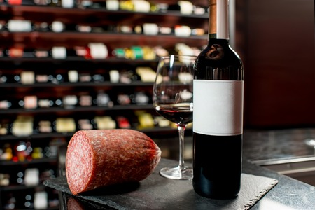 choise: Salamy sausage with red wine on the table in the restaurant or food market. Bottle with empty label to copy paste Stock Photo