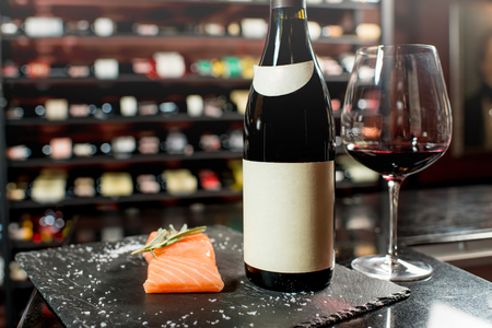 choise: Salmon steak with red wine on the board at the luxury supermarket or restaurant. Bottle with empty label to copy paste