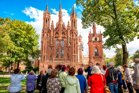 st  francis: Vilnius, Lithuania - September 21, 2016: Group of tourists in front of saint Anna gothic church in the old town of Vilnius city, Lithuania. This church is very popular tourist destination