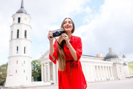 Portrait of a young female tourist with photo camera on the cathedral square in front of the famous basilica in Vilnius. Woman having great vacations in Lithuania Stock Photo