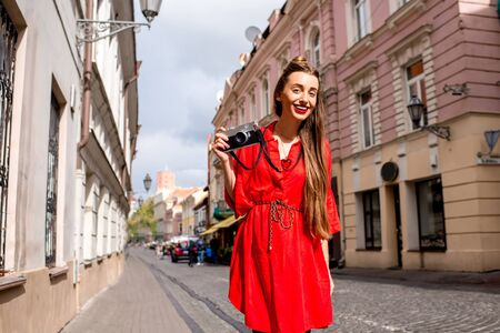 Portrait of a young female tourist with photo camera on the main pedestrian street in the old town of Vilnius. Woman having great vacations in lithuania Stock Photo