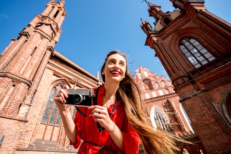 of assisi: Young female tourist with photo camera standing in front of the famous gothic church in the old town of Vilnius. Woman having great vacations in Lithuania