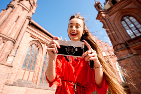 Young female tourist with photo camera standing in front of the famous gothic church in the old town of Vilnius. Woman having great vacations in Lithuania