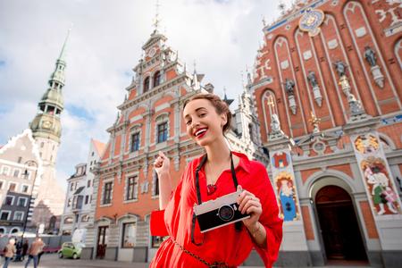 リガのメインの古い町の広場にフォト カメラで若い女性観光客の肖像画。ラトビアでの素晴らしい休暇を持って女性
