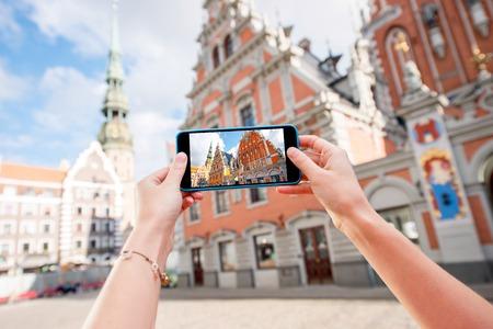 Fotografiando con teléfono inteligente las casas famosas de Blackheads y la iglesia de Peter en el centro del casco antiguo en Riga Foto de archivo - 69570497
