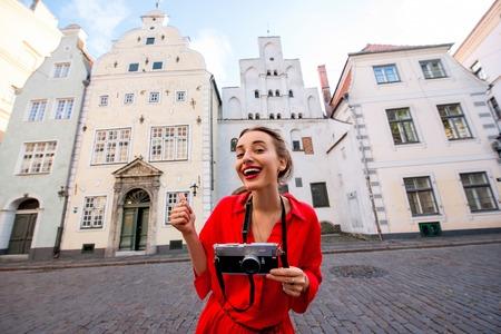 Portrait d'une jeune femme touriste avec appareil photo devant les trois célèbres frères anciennes maisons à Riga. Femme ayant de grandes vacances en Lettonie