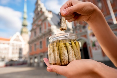 Female hands holding a jar with sprats in the center of Riga city. Riga is famous for its tasty golden and smoked fish called sprats.