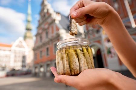femme, mains tenant un pot avec sprats dans le centre de la ville de Riga. Riga est célèbre pour ses savoureux sprats de poisson appelé or et fumés.