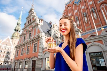 ラトビアの古い町の広場でリガのスプラットを食べる若い女性。リガの美味しい黄金と燻製魚スプラットと呼ばれるで有名です。 写真素材