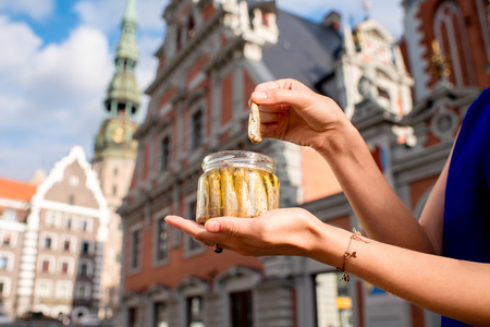 sprats: Female hands holding a jar with sprats in the center of Riga city. Riga is famous for its tasty golden and smoked fish called sprats.