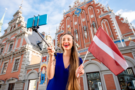 blackhead: Young female tourist making selfie portrait with latvian flag on the old town square in Riga. Woman having great vacations in Latvia