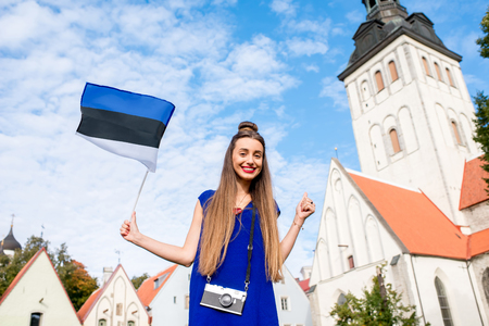 Portrait of a young female tourist with photo camera and estonian flag in front of saint Nicholas church in the old town of Tallinn. Woman having great vacations in Estonia Stockfoto