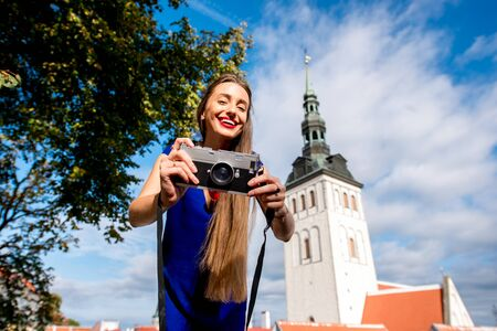 Portrait of a young female tourist with photo camera in front of saint Nicholas church in the old town of Tallinn. Woman having great vacations in Estonia Stock Photo