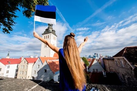 Young female tourist with estonian flag in front of saint Nicholas church in the old town of Tallinn. Woman having great vacations in Estonia