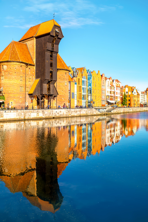 Morning view on the riverside of Motlawa river with beautiful buildings and famous historic gate of the old town in Gdansk, Poland Stock Photo