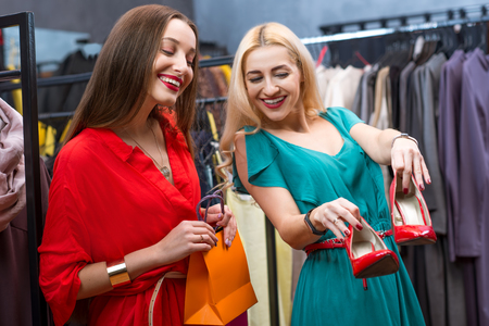 choise: Beautiful women choosing red shoes in the clothing store. Female friends having fun shopping in the boutique