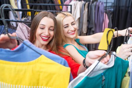 choise: Beautiful women choosing garments in the clothing store. Female friends having fun shopping in the boutique