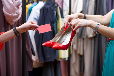 choise: Female hands holding red shoes with heels and credit card in the clothing store