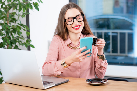 Businesswoman sitting with coffee, smartphone and laptop at the cafe