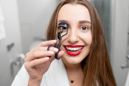 Woman with curler tool for eyelashes
